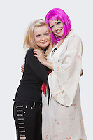 Portrait of two beautiful young woman embracing each other over white background