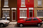 A window cleaner leathers down a freshly washed window of a terraced house in The Dingle district of Liverpool, England. Next door, the neighbour's favourite colour is obviously red - the colour of his home, his car and his favourite football team too - Liverpool FC. There is a sense of pride here, unlike other areas of the city where derelict streets are still common. Here, the paintwork is fresh, the cars are spotless and the red house has a burglar alarm on the wall. The sign there is a degree of wealth in this neighbourhood.