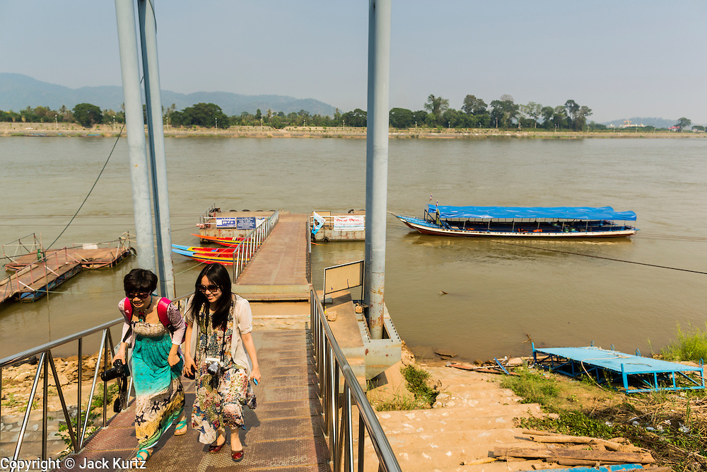 26 APRIL 2014 - CHAING SAEN, CHIANG RAI, THAILAND: Chinese tourists walk back to shore after a boat ride in the Golden Triangle, a village in Chaing Saen district of Chiang Rai province, Thailand. The Golden Triangle is where Thailand, Myanmar (Burma) and Laos meet on the Mekong River. Chinese businesses play an increasingly important role in the Chiang Rai economy. Consumer goods made in China are shipped to Thailand while agricultural products made in Thailand are shipped to China. Large Chinese cargo boats ply the Mekong River as far south as Chiang Saen in the dry season and Chiang Khong when river levels go up in the rainy season.      PHOTO BY JACK KURTZ