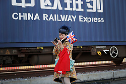 © Licensed to London News Pictures. 18/01/2017. London, UK.  A woman in Chinese dress, holding a British union flag watches as the first direct rail freight train from China arrives at Barking Rail Freight Terminal east of London. The new service set off from China on the 3rd of January this year. London is now the 15th European city to join what the Chinese government calls the New Silk Route. Photo credit: Peter Macdiarmid/LNP