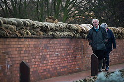 © Licensed to London News Pictures. 28/12/2015. Cawood, UK. An elderly couple walk alongside sandbags and a flood defence wall in the town of Cawood in North Yorkshire where flood water and rising tides have threatened the town on December 28, 2015. Several warnings of risk to life are sill in place in parts of Lancashire and Yorkshire where rainfall has been unusually high, causing heavy flooding. Photo credit: Ben Cawthra/LNP
