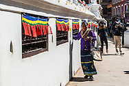 An old lady turns prayer wheels on the side on the Boudhanath stupa in Kathmandu, Nepal.