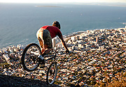 South African Trials Rider Andrew Guess finishes off the day with a practise session on Lions Head mountain, overlooking Robben Island in Cape Town. Image by Greg Beadle