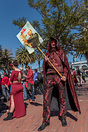 """A man dressed in all red brocade with sparkling cape holds a sign with a picture of Putin holding a """"baby Trump"""" at the San Francisco International Women's Day rally at Justin Herman Plaza. Many demonstrators wore red to show support for the """"Day without a Woman"""" strike."""