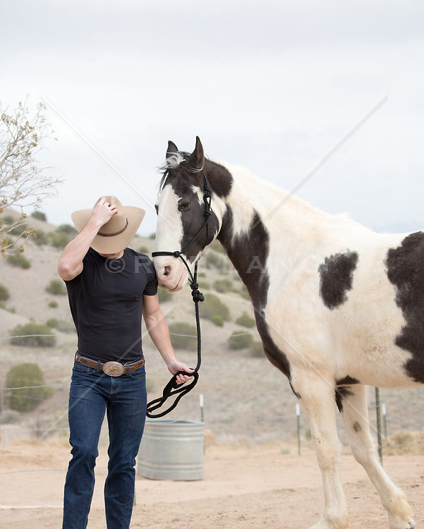 cowboy with a painted horse on a ranch