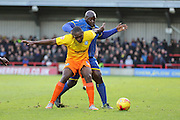 Bayo Akinfenwa of AFC Wimbledon and Anthony Stewart of Wycombe Wanderers tussle during the Sky Bet League 2 match between AFC Wimbledon and Wycombe Wanderers at the Cherry Red Records Stadium, Kingston, England on 21 November 2015. Photo by Stuart Butcher.