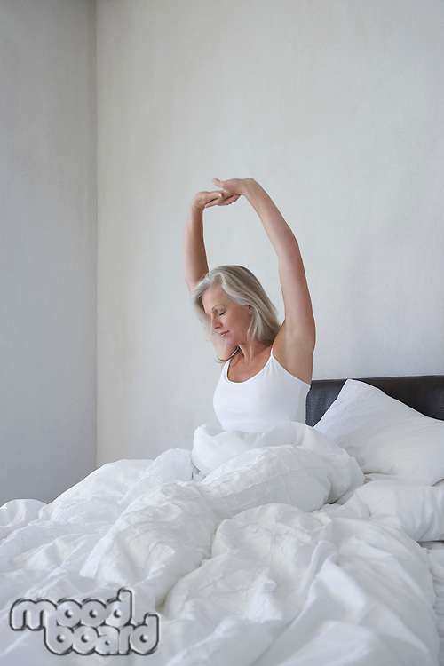 Mature woman in pyjamas sitting in bed under cover stretching in the morning