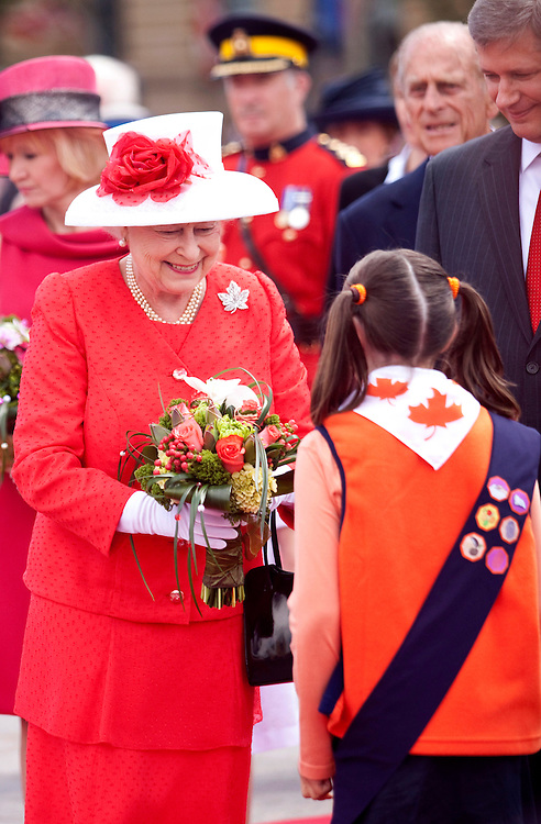 Queen Elizabeth II receives flowers from a girl guide as she arrives on Parliament Hill for Canada Day celebrations in Ottawa, Ontario, July 1, 2010. The Queen is on a 9 day visit to Canada. <br /> AFP/GEOFF ROBINS/STR