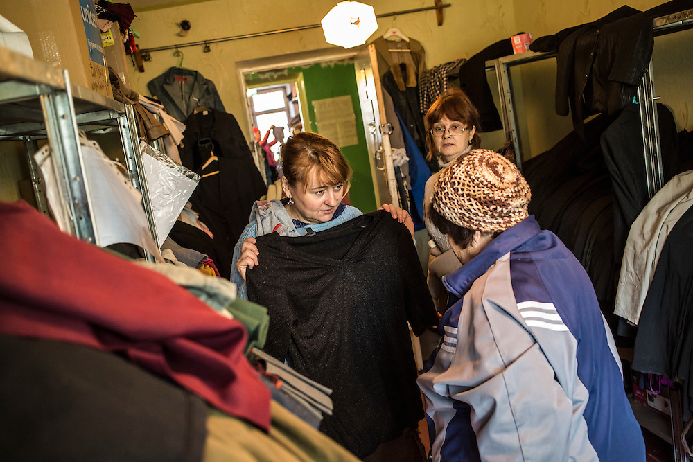 DNIPROPETROVSK, UKRAINE - OCTOBER 10: A volunteer helps a client choose from donated winter clothes which are available for people who fled with few belongings at The Aid of Dnipro, a charity organization providing assistance to displaced people from Eastern Ukraine, on October 10, 2014 in Dnipropetrovsk, Ukraine. While the charity has received many donations of clothes and toys, they are having a difficult time providing enough food to those in need. The United Nations has registered more than 360,000 people who have been forced to leave their homes due to fighting in the East, though the true number is believed to be much higher. (Photo by Brendan Hoffman/Getty Images) *** Local Caption ***