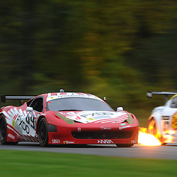 The AIM Autosport Team FXDD with Ferrari Ferrari 458 driven by Emil Assentato and Jeff Segal of the United States passes a fire-spitting Team Sahlen Mazda RX-8 during the Grand-Am Rolex Sports Car Series Championship weekend at Lime Rock Park in Lakeville, Conn.