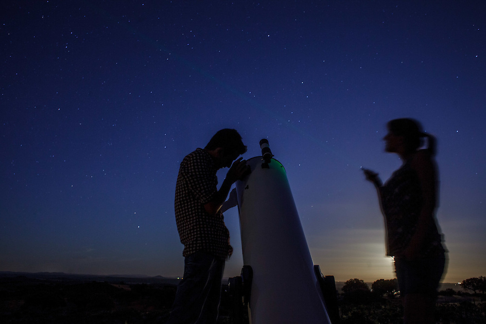 A couple looking at the sky through a telescope while drinking a glass of wine, near Reguengos de Monsaraz , in the Alentejo region, in Portugal.
