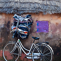 Bicycle with Clothes on Handle Bars Leaning Against A Hut in Tamale, Ghana