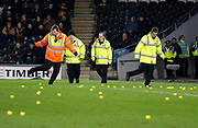 Stewards clearing the pitch of yellow balls thrown by Hull fans in protest at the ownership of the club by the Allam family during the EFL Sky Bet Championship match between Hull City and Sheffield Utd at the KCOM Stadium, Kingston upon Hull, England on 23 February 2018. Picture by Paul Thompson.