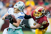 Washington Redskins' cornerback E.J. Biggers grabs the facemask of Dallas Cowboys' wide receiver Cole Beasley during second quarter action at FedEx Field in Landover, Maryland on December 28, 2014.  UPI/Pete Marovich