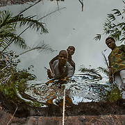 Sonny Olulu, the youth leader in Kegbara Dere (center), and other members of the community are reflected in a containment pond full of oil in a swamp near the community. The site is one of four where Amnesty International found high levels of oil contamination in September despite the Nigerian government's claim that the clean up was finished in 2014. Jesse Winter photo.