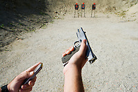 Man loading hand gun at firing range, focus on hands