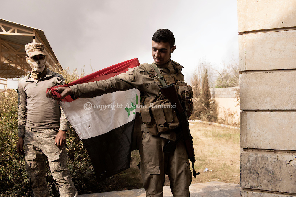 Iraq, Qayyara: On October 2016 a fighters of Iraqi tribe sunny militia dresses the Iraqi flag as mantel. Alessio Romenzi