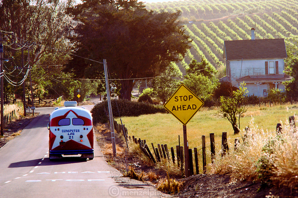 Napa Computer Bus: In 1983 more than 3,000 school children throughout California's Napa Valley were treated to hands-on experience with ATARI computers. A refurbished school bus with 17 ATARIs on board circulated among the 21 public schools in the district, giving each fourth-, fifth- and sixth-grader several opportunities to work with Atari's PILOT language. An old school bus (circa 1953), provided by the district, was painted red, white and blue and named the Napa Valley Unified School District Computer Lab. The lab accommodated 32 students at a time with each child sharing a 400. Each learning station also included an 11-inch Quasar television for video display and a cassette recorder for storage. The instructor's station was equipped with a disk drive and dot matrix printer as well as a TV and tape recorder. Seen here in rural Napa County.