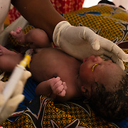 Midwife, Viola Nizigiyimana, applying an ointment to the eyes of a healthy baby boy to guard against infection moments after he was born at a Médecins Sans Frontières (MSF) health centre at the Mbera camp for Malian refugees in Mauritania, on 5 March 2013. (In keeping with tradition, the baby will not be named until he is a week old.)