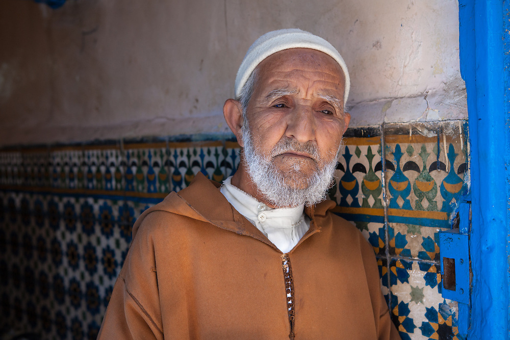 An old muslim man, wearing a traditional orange djellaba, in the old medina of Essaouira, Morocco.