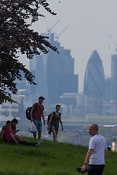 People enjoy the hazy sunshine partially obscuring the City skyline in London, seen from Maze Hill, Greenwich as Mayor Sadiq Khan announces air toxicity alerts for the Capital. London, May 08 2018.