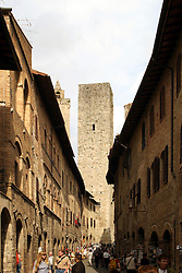General scene along the main shopping street, Via S. Giovanni, with one of the town's famous medieval towers in the background.