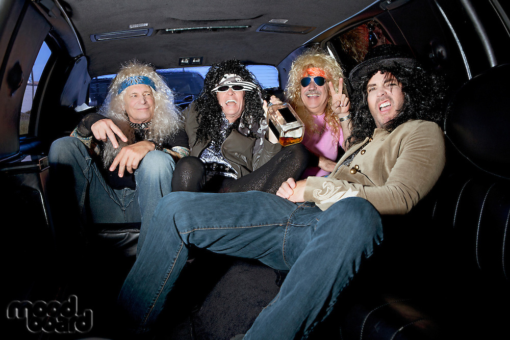 Group of friends enjoying alcohol in limousine