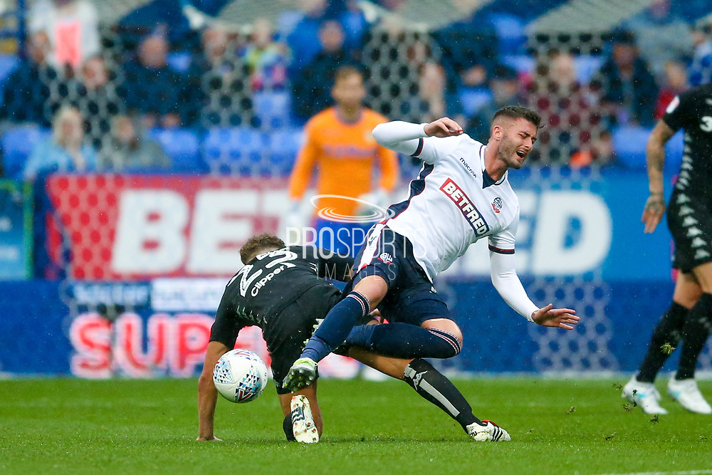 Leeds United midfielder Kalvin Phillips (23) fouls Bolton Wanderers striker Gary Madine (14)  during the EFL Sky Bet Championship match between Bolton Wanderers and Leeds United at the Macron Stadium, Bolton, England on 6 August 2017. Photo by Simon Davies.