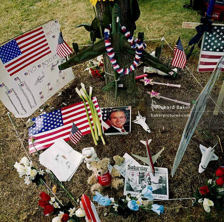 At the foot of a tree located opposite the charred Pentagon building days after the September 11th attacks in New York and Washington DC, children have made a makeshift memorial by placing a garland around the model of a military B52 bomber, a NASA space Shuttle,  portrait of a smiling president George W Bush and their own interpretation of the attacks on the Twin Towers - with airliners flying towards those symbols of capitalism.  Icons of American technology and patriotic success lie on the ground here beneath the tree near Arlington military Cemetery. In a show of unity, many of those gathered on the grass to view the damage done by terrorists worked for the government or defence organisations, their Hawkish rhetoric appearing to suggest heavy-handed retaliation on those held responsible.