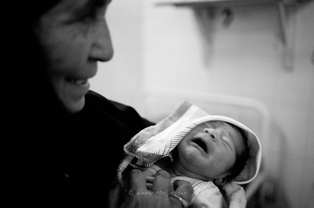 A mother in law is proudly holding the newborn baby her daughter in law just delivered. Qatar hospital, Karachi, Pakistan 2010