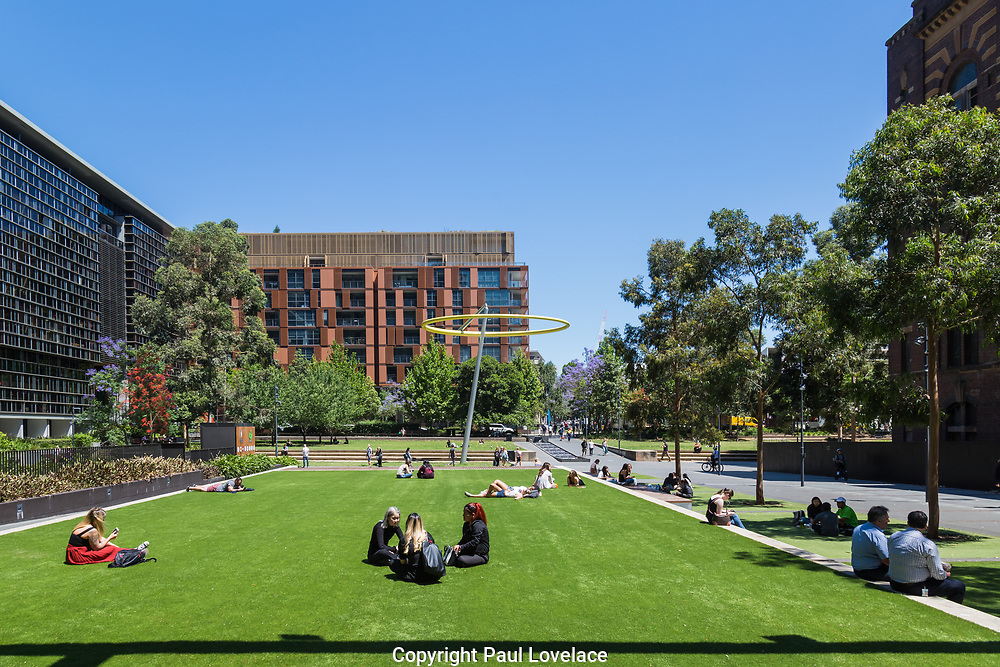 General Views showing  Chippendale Green, Sydney, which is built around One Central Park. The building itself was designed by award-winning Parisian architect Jean Nouvel and the vertical gardens designed by the artist and botanist Patrick Blanc, Chippendale, Sydney, Australia. The residential building has been named best tall building in the world in June 2014. A massive silver heliostat hangs from One Central Park to redirect light to the ground below. The unique steel heliostat is specifically designed to reflect sunlight to another area. The heliostat seen in action reflecting sunlight.