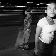 A prostitute looks on while waiting for customers near Victory Monument in Phnom Penh.