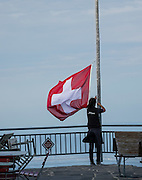 Lowering the flag of Switzerland at Berggasthaus Alter Säntis at sunset. The flag of Switzerland is red with a white equilateral cross in the center. It is one of only two square sovereign-state flags (the other being the flag of Vatican City). In contrast, the civil and state ensign of Switzerland, used by Swiss vessels and non-governmental bodies, is rectangular with the more common proportions of 3:2. Use of the white cross as a military ensign (attached to the cantonal flags in the form of strips of linen) has been used in the Old Swiss Confederacy since the 1300s, but the modern design was first used in 1800 during Napoleon's Hundred Days, and was introduced as official national flag in 1889. Photographed at Berggasthaus Alter Säntis, atop Säntis (2502 m / 8218 feet), the highest peak of the Alpstein range and the Appenzell Alps, located in northeast Switzerland, Europe.