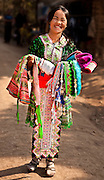 A smiling Hmong girl displaying festival costumes of the villagers.  The colorful outfits are worn at the time of the New Year festivities celebrated by the Hmong and other hill tribes in northern Laos.<br /> (Photo by Matt Considine - Images of Asia Collection)