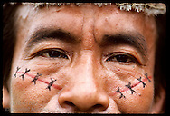 Close up of Kanamari man's face painted in tribal pattern at village of Tres Unidos, Amazonas Brazil