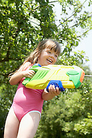 Girl in park shooting pump action water pistol