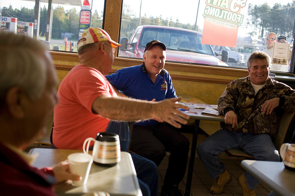 "On most weekday mornings Rockingham Speedway owner Andy Hillenburg, in blue polo, gathers with local friends at the Citgo gas station outside of Rockingham, N.C., to shoot the breeze. They call it ""The Barbershop."" Pictured with Hillenburg are, from left, Bill Pattan and Bo Ussery."