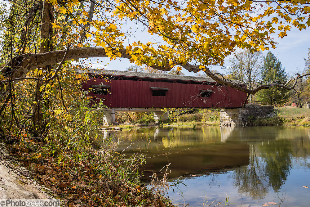 The 148-foot wooden Cataract Falls Covered Bridge was built in 1876 at the Upper Falls of Mill Creek (formerly known as Eel River) and was open to automobile traffic until 1988. The bridge now serves pedestrians and was extensively repaired starting in 2000. It is the only remaining covered bridge in Owen County. Cataract Falls State Recreation Area is an hour southwest of Indianapolis, near Cloverdale, Indiana, USA. The bridge was designed with a Smith's High Double Wood Truss (Smith Type 4), prefabricated in Toledo, Ohio and shipped disassembled for reassembly. Nice autumn foliage colors glowed for this photo in mid October 2015.