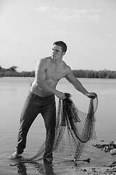 hot shirtless man fishing in The Everglades with a fishing net