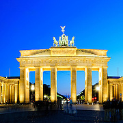 The Brandenburg Gate at dusk, with lights illuminating the monument and a deep blue sky. High resolution panorama.