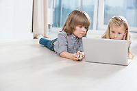Brother and sister using laptop on floor at home