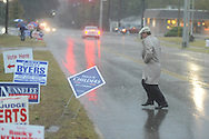 Dave Bell runs past campaign signs as voters go to the polls in the rain at the National Guard Armory in Oxford, Miss. on Tuesday, November 2, 2010.