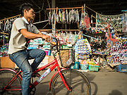 02 SEPTEMBER 2015 - BANGKOK, THAILAND: A man rides his bike past the back entrance into Bang Chak Market. The Bang Chak Market serves the community around Sois 91-97 on Sukhumvit Road in the Bangkok suburbs. About half of the market has been torn down, vendors in the remaining part of the market said they expect to be evicted by the end of the year. The old market, and many of the small working class shophouses and apartments near the market are being being torn down. People who live in the area said condominiums are being built on the land.         PHOTO BY JACK KURTZ