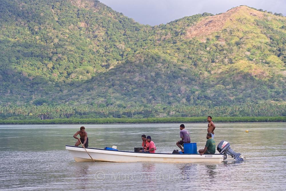 Fijian men in a small boat in Vanua Levu, Fiji.