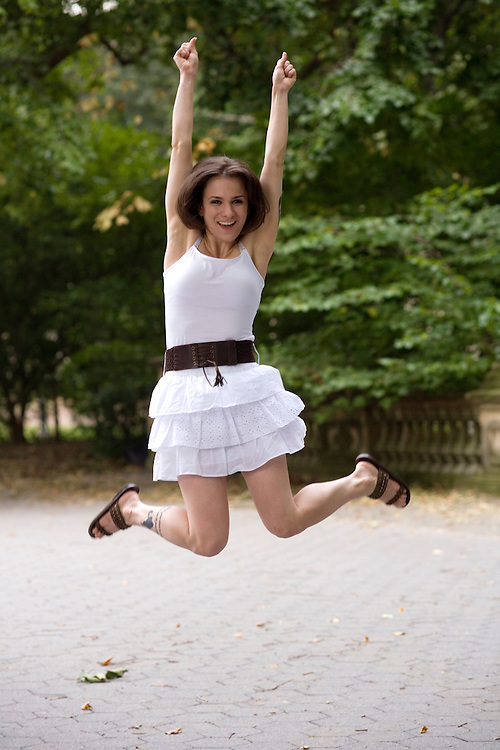 Jumping for joy! Mid 20's brunette caucasian woman jumps for joy to celebrate her victory, success and achievement.