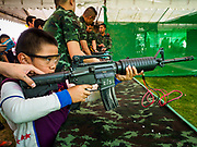"13 JANUARY 2018 - BANGKOK, THAILAND:      A Thai child fires a BB gun that looks like a M4 assault rifle during Children's Day activities at the Royal Thai Army's King's Guard 2nd Cavalry Camp in central Bangkok. Children's Day is called ""Wan Dek"" in Thai. Many government offices and military bases hold special activities for children as do shopping malls.  PHOTO BY JACK KURTZ"