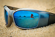 The Mokulua Islands and a Santa hat are reflected in sunglasses on Lanikai Beach in Hawaii.