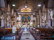18 SEPTEMBER 2016 - BANGKOK, THAILAND: People walk through the sanctuary of Santa Cruz Church before the church's 100th anniversary mass. Santa Cruz Church was establised in 1769 to serve Portuguese soldiers in the employ of King Taksin, who reestablished the Siamese (Thai) empire after the Burmese sacked the ancient Siamese capital of Ayutthaya. The church was one of the first Catholic churches in Bangkok and is one of the most historic Catholic churches in Thailand. The first sanctuary was a simple wood and thatch structure and burned down in the 1800s. The church is in its third sanctuary and was designed in a Renaissance / Neo-Classical style. It was consecrated in September, 1916. The church, located on the Chao Phraya River, serves as a landmark for central Bangkok.       PHOTO BY JACK KURTZ