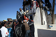 Tunisia's Ras Jdir main border crossing with Libya is overwhelmed by thousands of migrant workers fleeing unrest and faces a humanitarian crisis. Seen from Tunisia's side, Egyptians are waiting on the Lybian side of the border while a fainted man is pulled from the compact crowd and passed over the border. 1st March 2011.