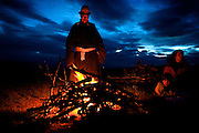 A Mongolian guide lights a bonfire in the grassland attended by autistic child Rowan, 5, and his mother Kristin..Rowan's parents believe horses and shamans can unlock their son's autistic mind. This is their journey of discovery across Mongolia on horseback. .The story is published by the Sunday Times and accompany text by Tim Rayment.